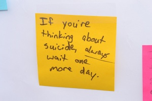 A post-it note with the words 'If you're thinking about suicide, always wait one more day'